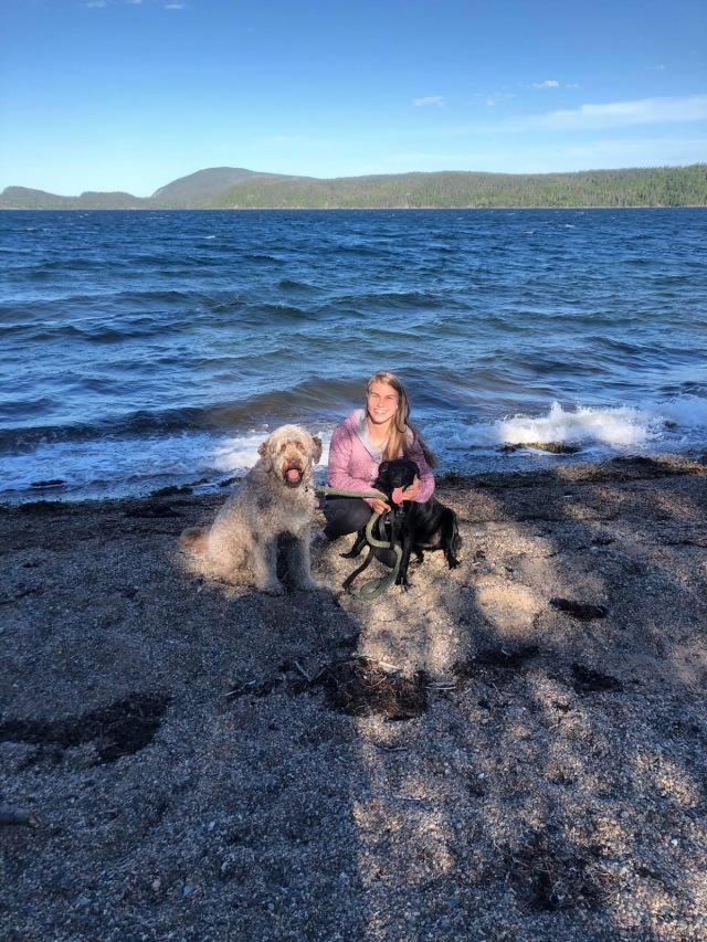 Rachel kneeling by the water with her two dogs